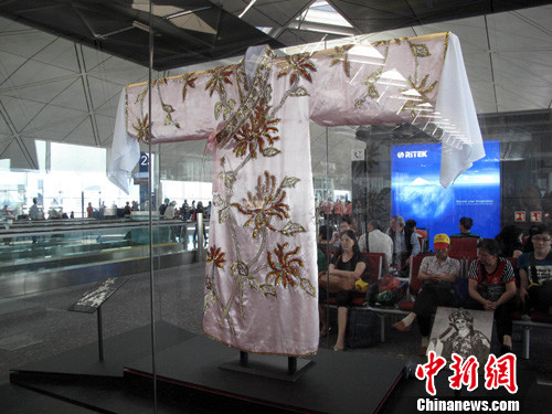 在香港国际机场候机室展出的一批珍贵舞台戏服和道具吸引的旅客欣赏。中新社发 洪少葵 摄