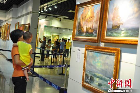 市民带着孩子前来观看俄罗斯油画展 周潇男 摄