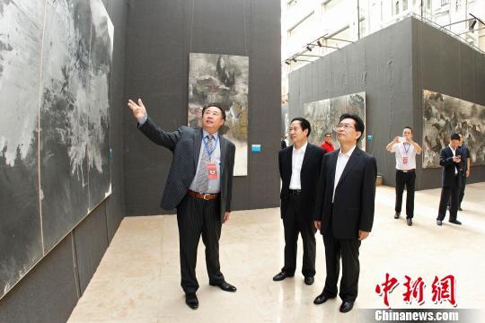 """中国文化建设协会副会长官景辉(右)在王林旭的陪同下参观""""中国文化走向世界""""王林旭当代艺术展。"""