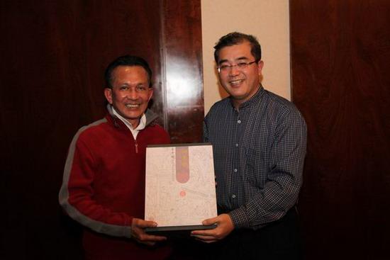 广西壮族自治区旅游局局长陈建军(右)向泰国体育旅游部次长赠送广西旅游纪念品