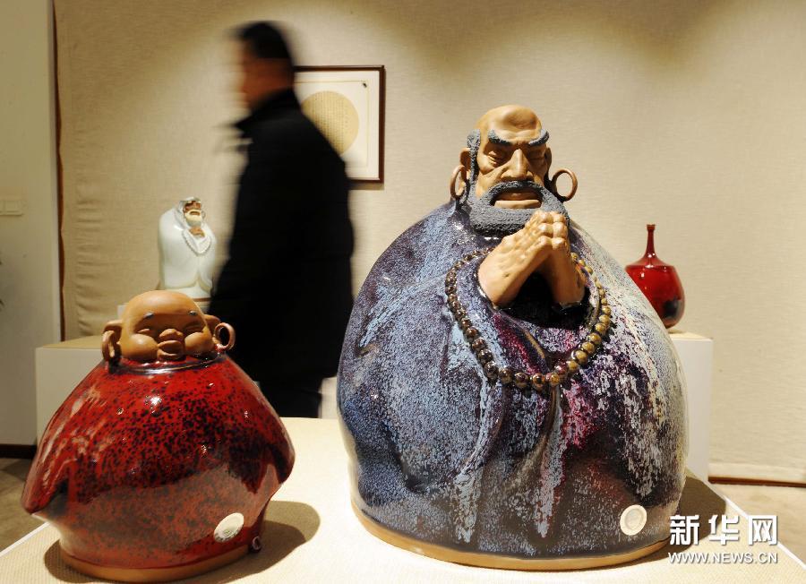 (1)1月9日,一名参观者从展出的作品旁走过。