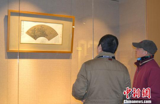 1月15日,两位参观者在欣赏唐寅作品《读书图》。中新社发 苏路程 摄