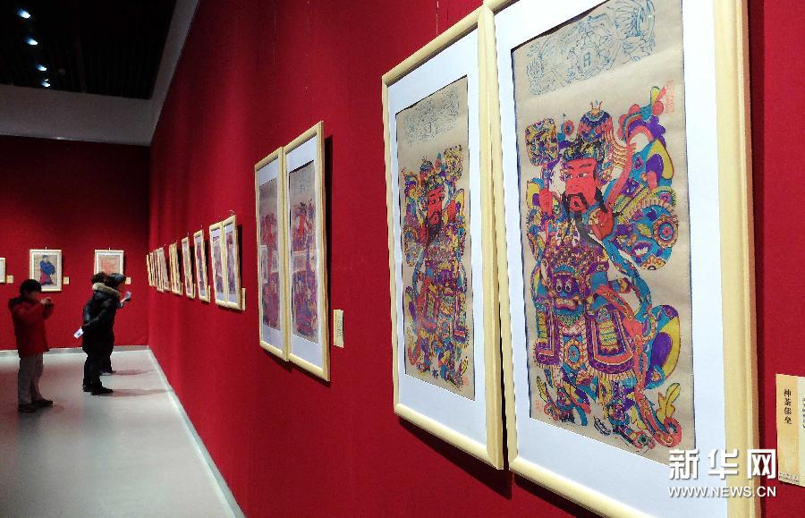 (1)1月28日,参观者在观看一组门神主题年画。