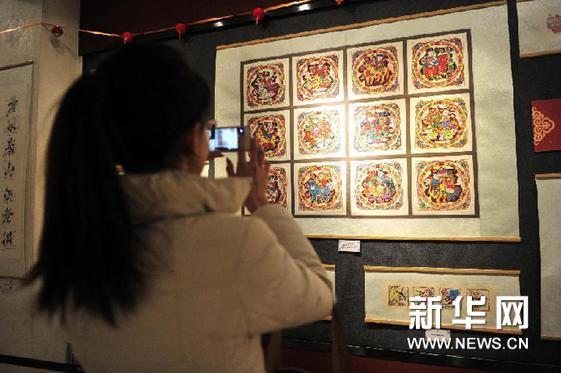 2月7日,拉萨市民在用手机拍摄展出的年画。新华网图片 刘坤 摄