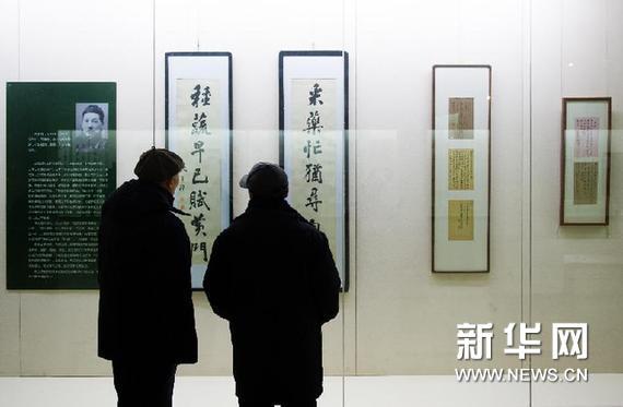 2月10日,两名书法爱好者在观赏展出的成多禄书法作品。新华网图片 许畅 摄