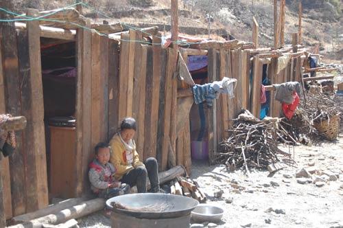孩子手中的碗里是米饭和榨菜 母亲就吃了一个土豆