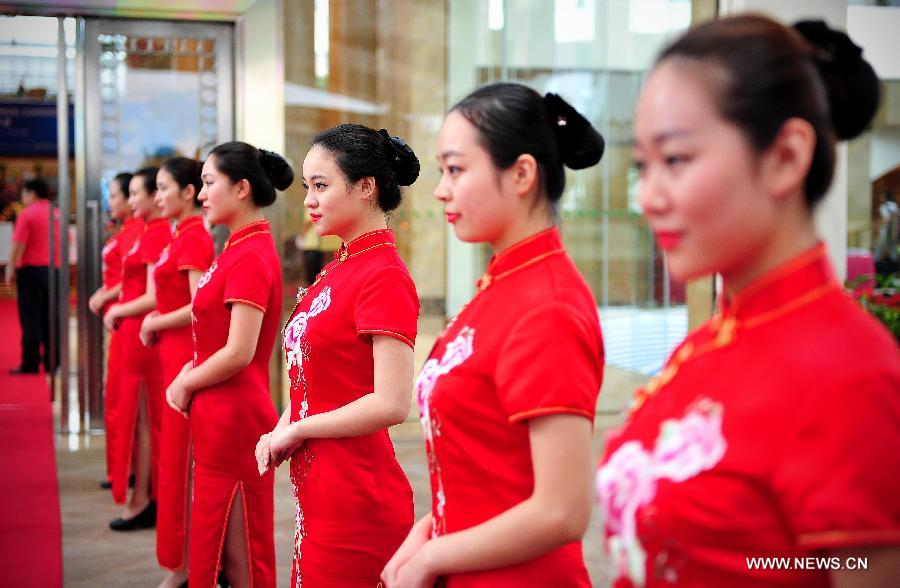 Photo taken on April 7, 2014 shows the ritual girls waiting for guests outside the Boao International Conference Center in Boao, south China
