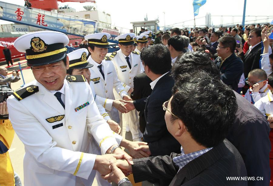 Crew members of Chinese research vessel and icebreaker Xuelong (Snow Dragon) are greeted after return to Shanghai, east China, April 15, 2014. The icebreaker returned to Shanghai on Tuesday, concluding the country