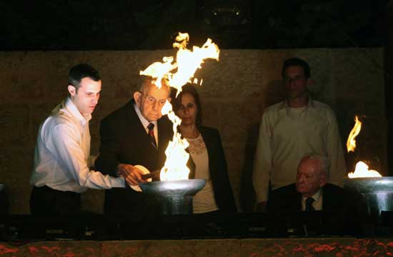 Holocaust survivor Tzvi Michaeli and his grandson light a torch during the opening ceremony of the Holocaust Remembrance Day at the Yad Vashem Holocaust Memorial in Jerusalem Jerusalem, Sunday, April, 27, 2014.