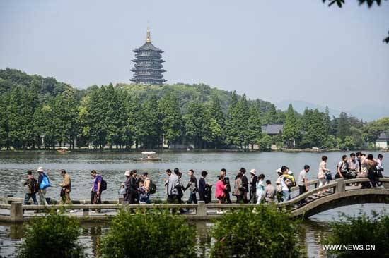 Visitors tour the West Lake scenic area in Hangzhou, capital of east China