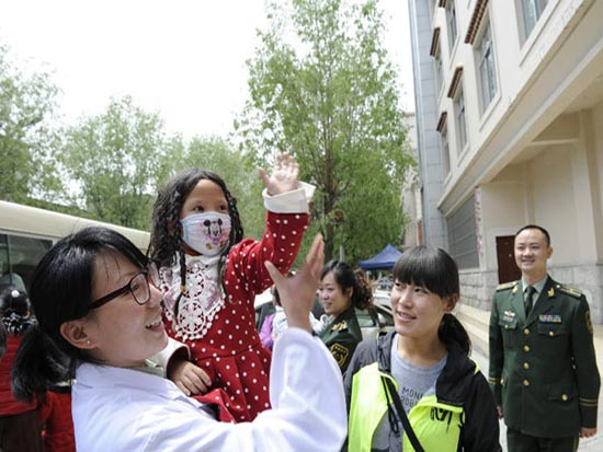 Metog bids farewell to the medical staff and volunteers after she leaves hospital on May 11, 2014. [Photo/Xinhua]
