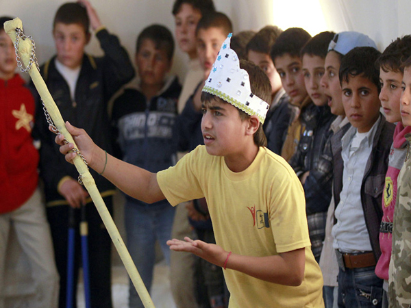 Syrian refugee Majd Ammari, 13, performs the role of King Lear during a rehearsal at the Zaatari Refugee Camp on March 8, 2014. (AFP photo by Khalil Mazraawi)