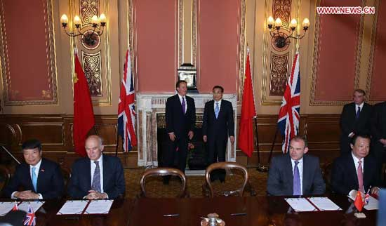 Chinese Premier Li Keqiang (4th R) and British Prime Minister David Cameron (3rd L) attend a signing ceremony of a number of bilateral cooperation documents after their annual meeting in London, Britain, June 17, 2014. (Xinhua/Pang Xinglei)