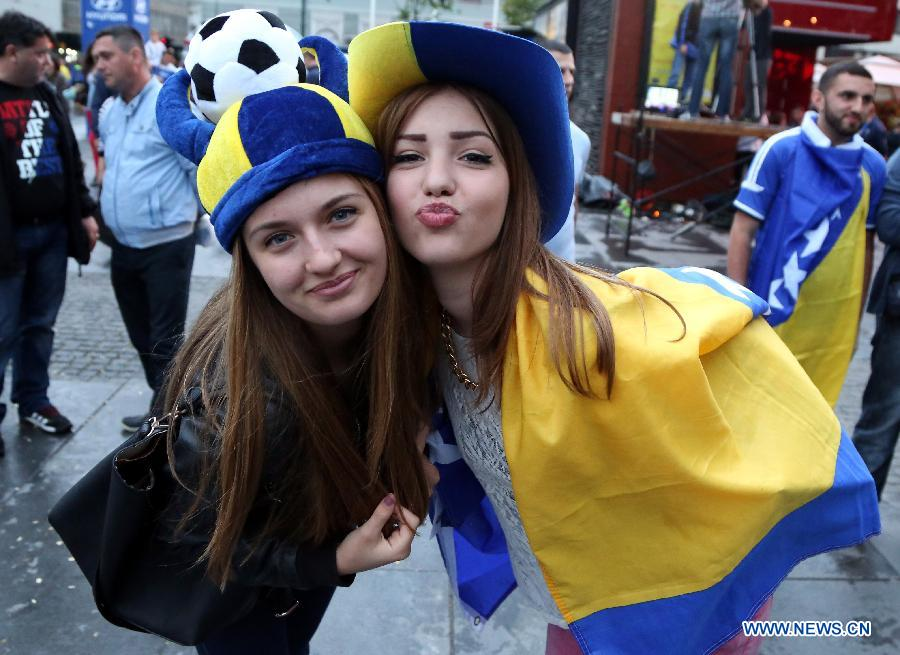 Fans cheer for the team as they watch the televised 2014 FIFA World Cup Group F match between Bosnia and Herzegovina and Iran, in front of the BBI Center at downtown Sarajevo, Bosnia Herzegovina, on June 25, 2014. Bosnia and Herzegovina won the match 3-1 but was disqualified for the knockout stage. (Xinhua/Haris Memija)