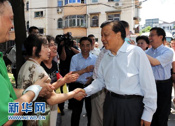 这是7月22日,刘云山在上海市普陀区桃浦镇莲花公寓居委会调研时同社区居民亲切握手。记者 饶爱民 摄