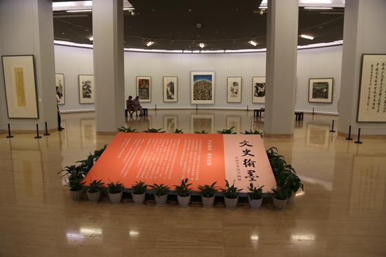 """展厅入口 中国美术馆8月8日讯 由国务院参事室、中央文史研究馆联合全国各地方政府参事室、文史研究馆,共同举办的""""文史翰墨——首届中华诗书画展"""" 于8月7日在中国美术馆启幕,展览集中展示了文史研究馆馆员近年来的诗、书、画创作成果。 中央文史研究馆设立于1951年,坚持""""敬老崇文,存史资政""""的工作宗旨,选聘馆员以""""德、才、望""""兼备为唯一标准。目前全国共有文史研究馆馆员2000余位。在这些馆员中,有饶宗颐、叶嘉莹、"""