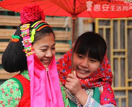接下来,新娘头顶系一个红绸球,垂下来的两条布条要遮住鼻子以下的部分。到此,惠女新娘的梳妆打扮基本完成。