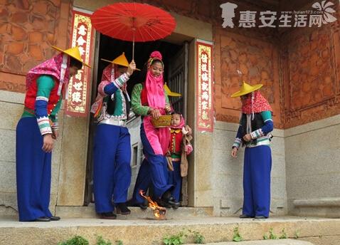 """新娘穿戴整齐后,就吃下一碗""""米丸""""。在两个伴娘和两个花童的簇拥下,她一手拿手绢,一手撑红伞,跨过事先点燃的碳炉,就表示出嫁了。新娘从娘家出门后,不能回头看,不然会影响夫妻关系。"""