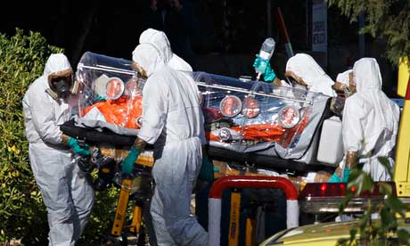 Paramedics wearing biological isolation suits carry Miguel Pajares in to hospital in Madrid. Photograph: Reuters