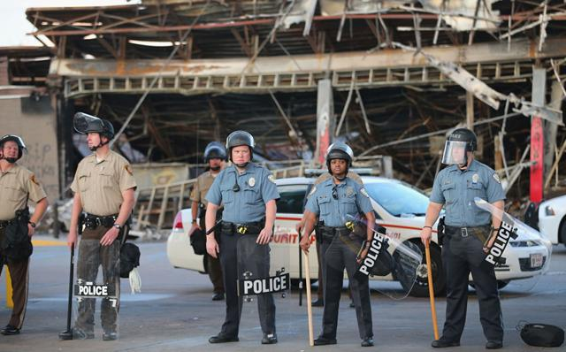 Police guard a Quick Trip gas station that was burned yesterday when protests over the killing of 18-year-old Michael Brown turned to riots and looting on August 11, 2014 in Ferguson, Missouri.