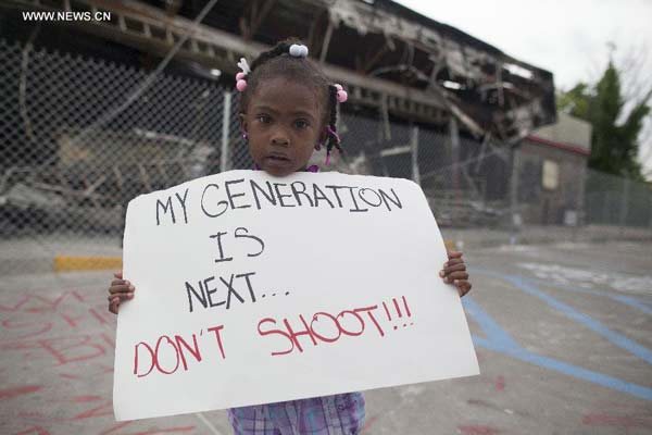 A girl holds a placard during a protest in Ferguson, Missouri, on Aug. 15, 2014. Police in Ferguson in the U.S. state of Missouri, where unrest has erupted since 18- year-old Michael Brown was killed last Saturday, accused the African American teen on Friday of robbing a convenience store shortly before he was shot dead by a police officer. (Xinhua/Marcus DiPaola)