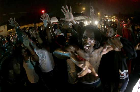 People defy a curfew Sunday, Aug. 17, 2014, before smoke and tear gas was fired to disperse a crowd protesting the shooting of teenager Michael Brown last Saturday in Ferguson, Mo. Brown