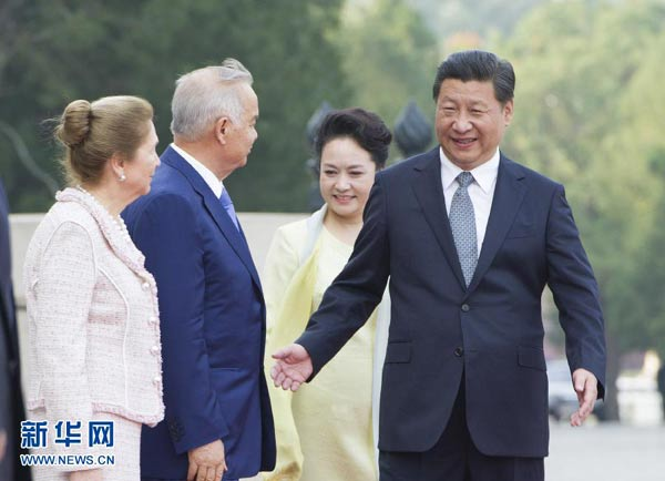 Chinese President Xi Jinping (1st R) and his wife Peng Liyuan (2nd R) greet visiting Uzbekistan