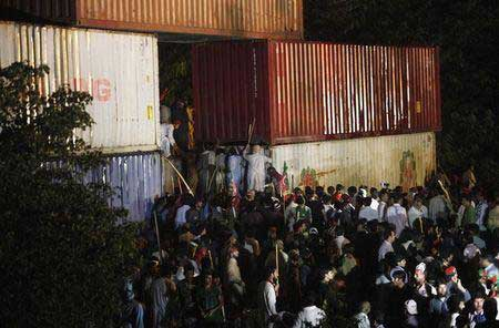 Supporters of former international cricketer Imran Khan, chairman of the Pakistan Tehreek-e-Insaf (PTI) political party, climb on container barricades as they participate during a Freedom March to the parliament house in Islamabad August 19, 2014.