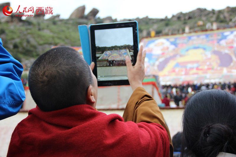 A 500-square-meter traditional Tibetan painting of the great Buddha is positioned on a hillside near Drepung Monastery.