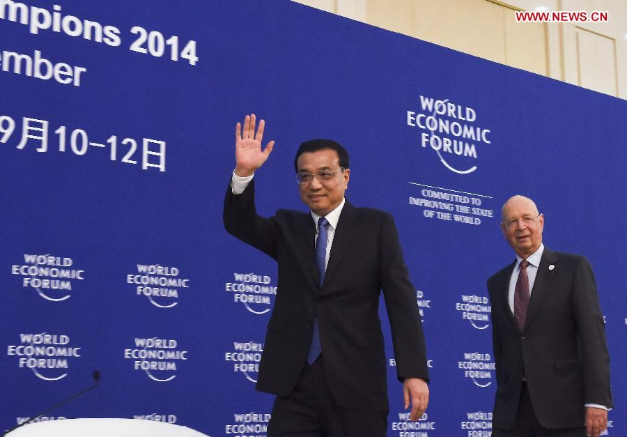 Chinese Premier Li Keqiang (L) and Klaus Schwab, founder and executive chairman of the World Economic Forum (WEF), walk into the conference hall of a meeting ahead of the Summer Davos forum in Tianjing Municipality, north China, Sept. 9, 2014. (Xinhua/Li Xueren)