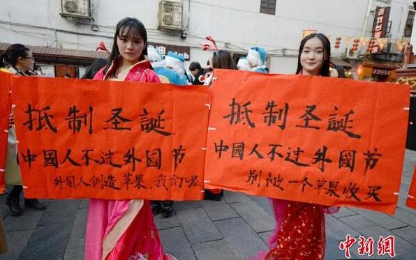 """12月24日,湖南一高校学生身着汉服来到长沙太平街的圣诞活动现场,手举""""抵制圣诞节""""等标语"""