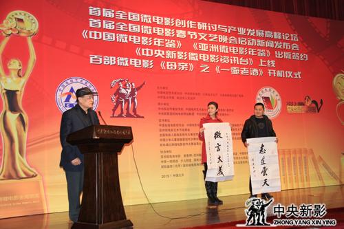 优秀演员赵钢、优秀青年演员李婧上台接受李春明将军(左一)的书法作品捐赠