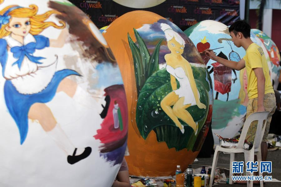 参赛者在硬纸制彩蛋上进行绘画创作.当日,菲律宾奎松城举行巨型