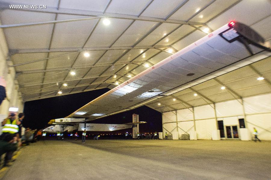 Ground crew members gather to push the Solar Impulse 2, the world
