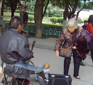 不知不觉,伯伯已经演奏完了好几首曲子。路人们纷纷献出爱心,只见一位老奶奶从包里拿出一些钱,放进了伯伯身前的桶里。