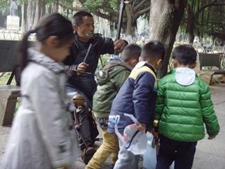 看,一群小朋友也来了,他们纷纷拿出自己的零花钱放进桶里。盲人伯伯虽然看不见,但他分明感受到人们热忱的爱心,他唱的更深情、更动听了!