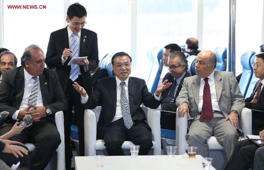 Chinese Premier Li Keqiang (C) talks with Chinese and Brazilian representatives from manufacturing and financial sectors as he takes a ride on a Chinese-made ferry boat in Rio De Janeiro, Brazil, May 20, 2015. (Xinhua/Pang Xinglei)