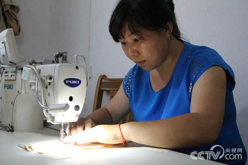 赖秋平在家用电动缝纫机为工业园区的一家纺织企业做
