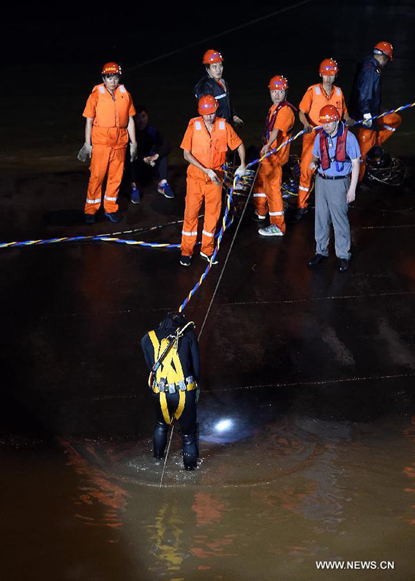 Rescuers work at the site of the overturned passenger ship in the Jianli section of the Yangtze River in central China
