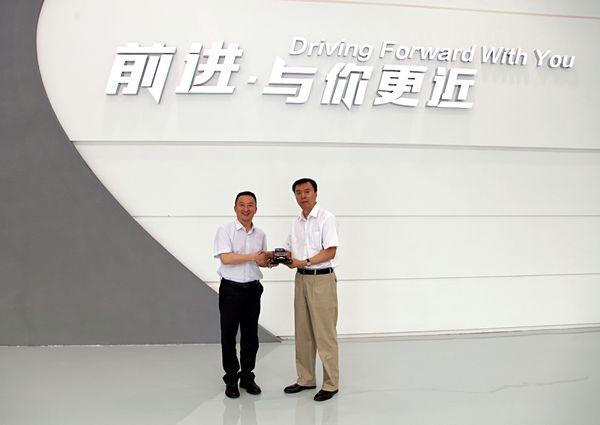 长安汽车副总裁李伟(左)向中央电视台副总编辑程宏赠送车模