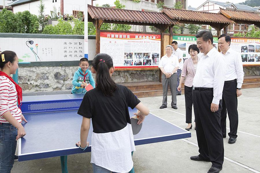 Chinese President Xi Jinping watches local children playing ping pang ball in a community center in Zunyi, southwest China