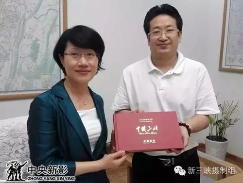 杨书华总导演向谭家玲副市长赠送他执导的大型文献纪录电影《中国三峡》的宣传册