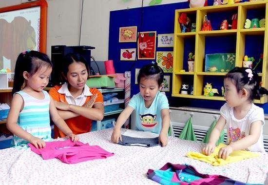 图:幼儿园宝宝唱着儿歌叠衣服