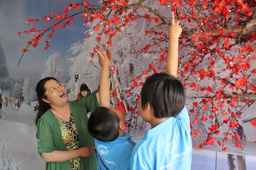 李银环指导学生观察画上的植物。