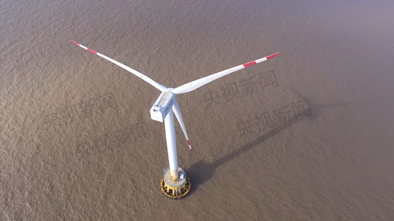 """东海大桥和它侧面海面上的风力发电场 全长32.5公里的东海大桥连接着上海浦东和洋山深水港,从空中俯瞰这座跨海大桥,水天一色,大桥一直延伸到天际线的尽头,分布在大桥两侧海面上的风车""""森林"""",就是东海大桥海上风力发电项目,它是国内第一个也是欧洲以外第一个海上风电场,总投资40."""