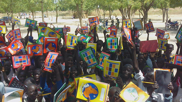 Children displaying the books donated to them by ASCOVIME.