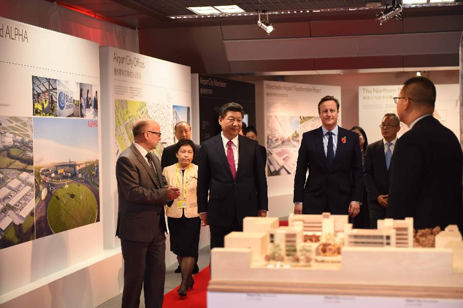Chinese President Xi Jinping (2nd L, front), accompanied by British Prime Minister David Cameron (2nd R, front), visits an exhibition at the airport city in Manchester, Britain, Oct. 23, 2015. (Xinhua/Zhang Duo)