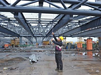 图2为:昆明南站施工人员每隔1小时就要对屋面钢结构吊装提升进行测量.