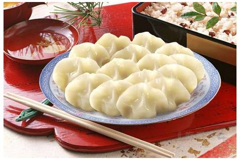 "On the Eve, the whole family sits together busily making ""jiaozi"", a kind of stuffed"