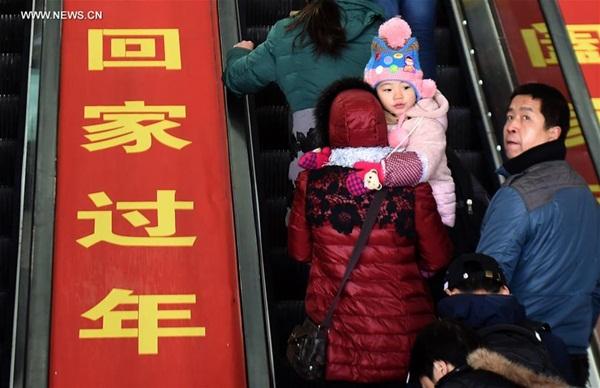 تنتظر طفلة القطار في المحطة بهانغتشو مع والديها، 24 يناير